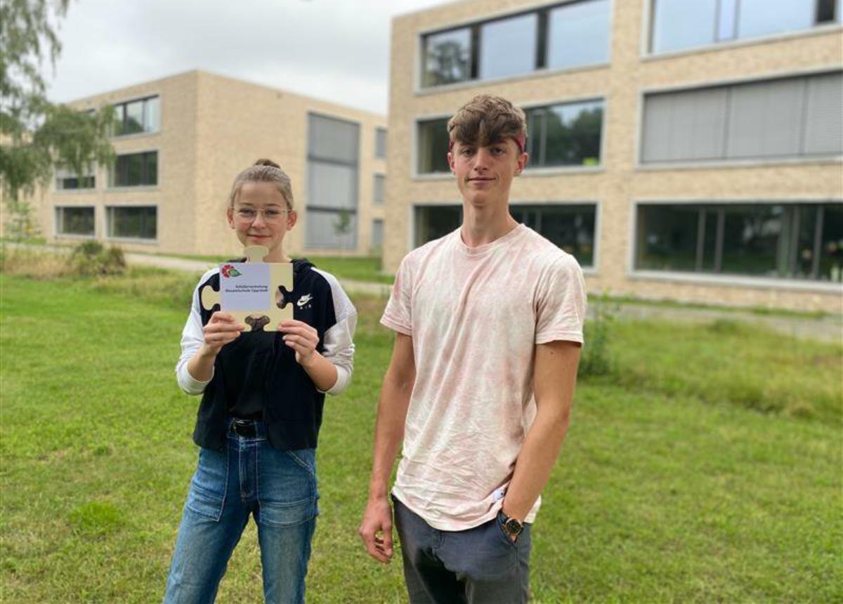 Zwei Schüler auf Wiese vor Schule