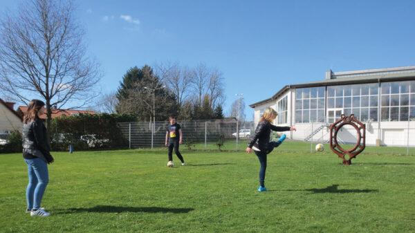 Jugendliche spielen mit Fußball auf Wiese