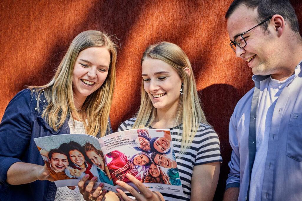 Junge Menschen, die in Broschüre schauen