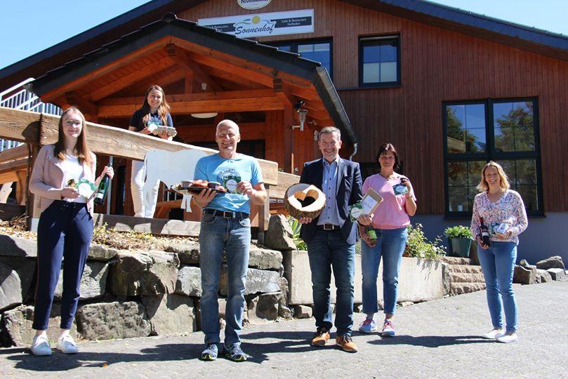 Mehrere Personen vor Holzhaus zeigen regionale Produkte