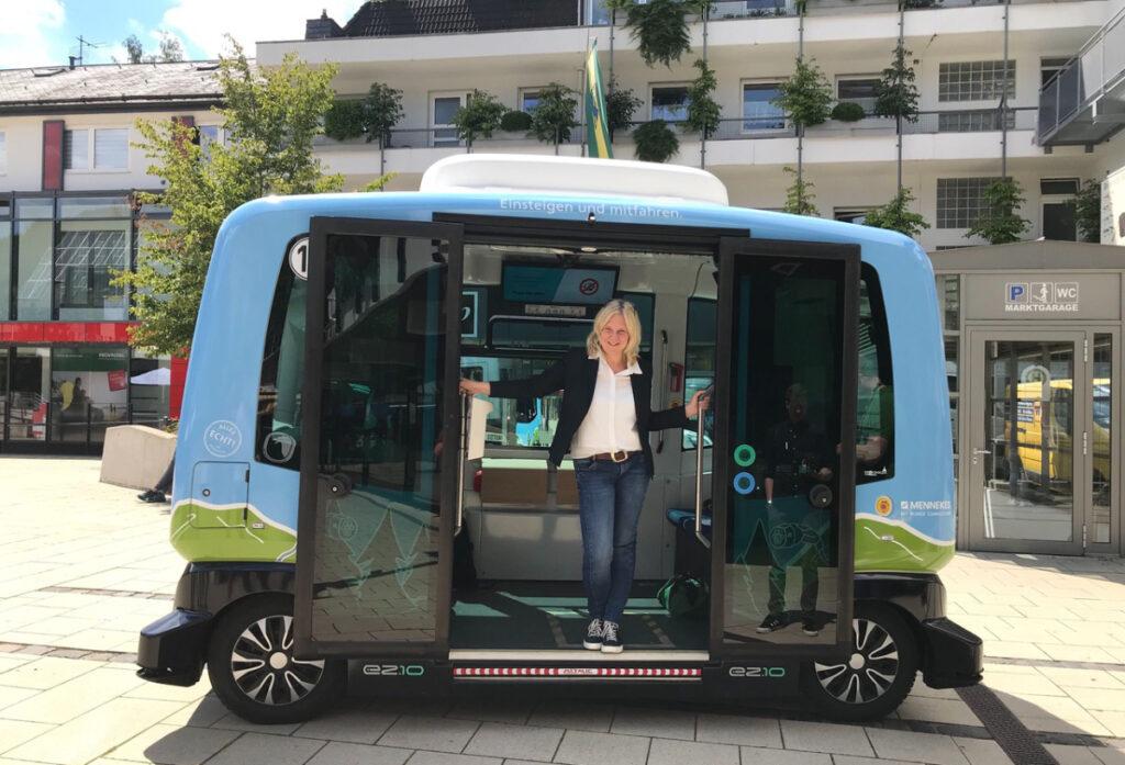 Autonomer Bus auf Platz, Frau steht in Tür