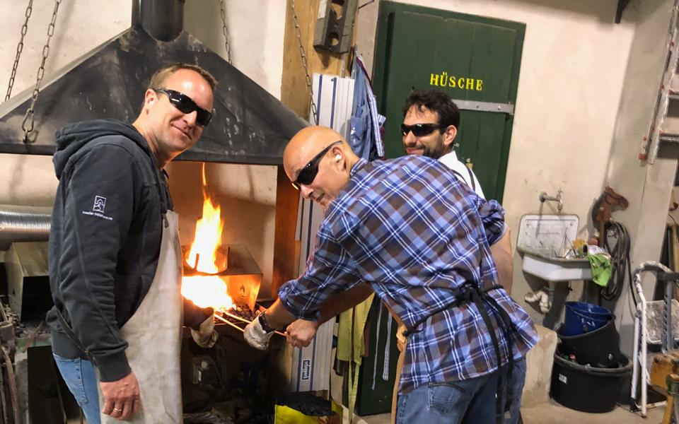 Drei Männer mit Schutzbrillen am Schmiedefeuer