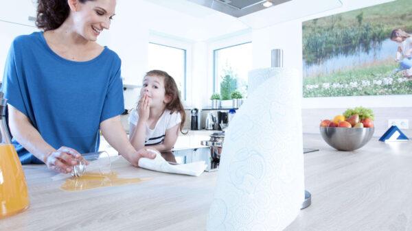 Mutter und Tochter wischen Orangensaft in Küche auf