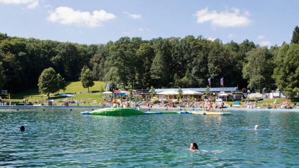 Blick auf eine Wasserbecken mit Schwimmern, Wald im Hintergrund