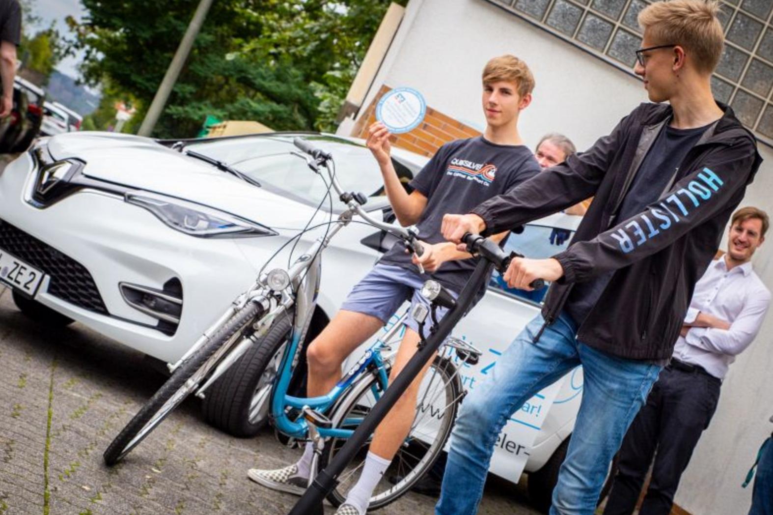Jugendliche neben/auf E-Fahrzeugen