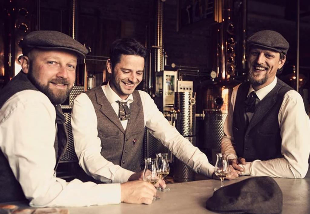 Drei Männer in Western-Style stehen mit Whisky an einer Theke