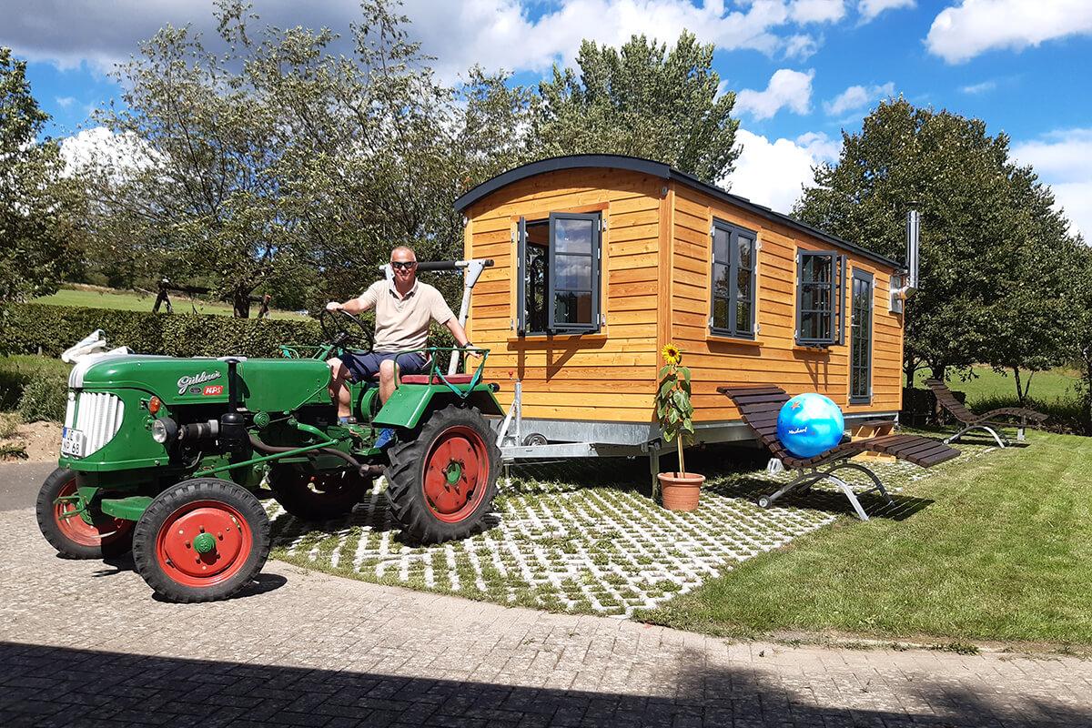 Mann auf Traktor zieht Holzwagen