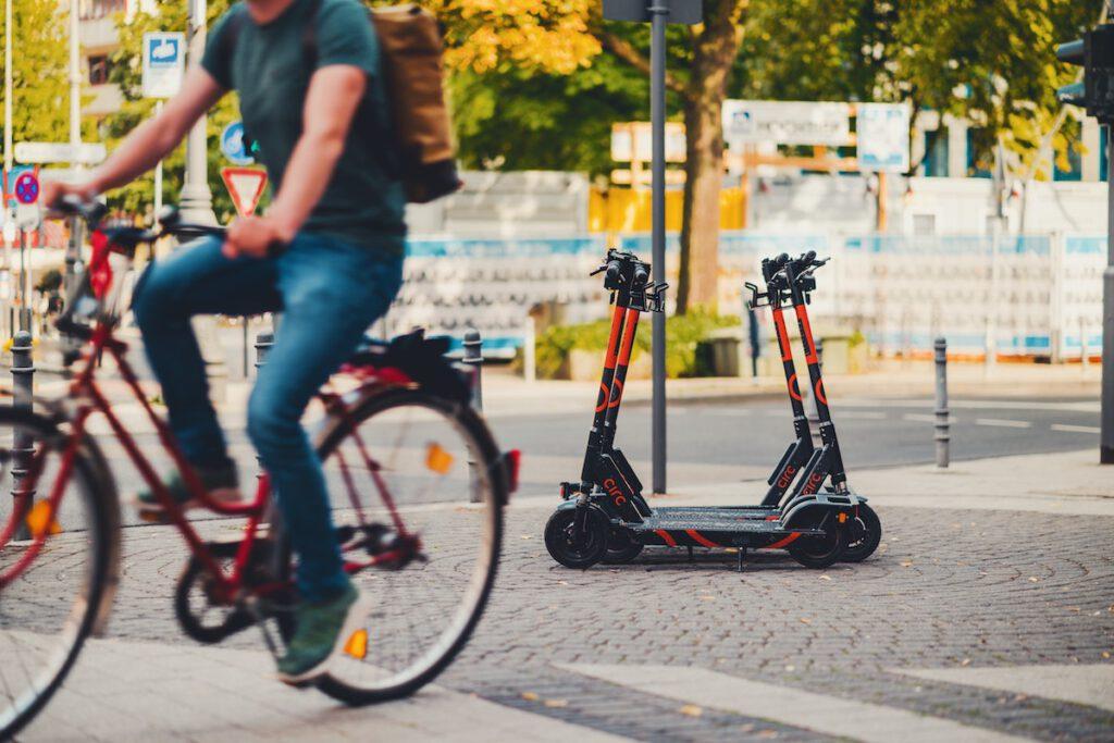 Ein Mann fährt auf einem Fahrrad. Im Hintergrund stehen E-Scooter