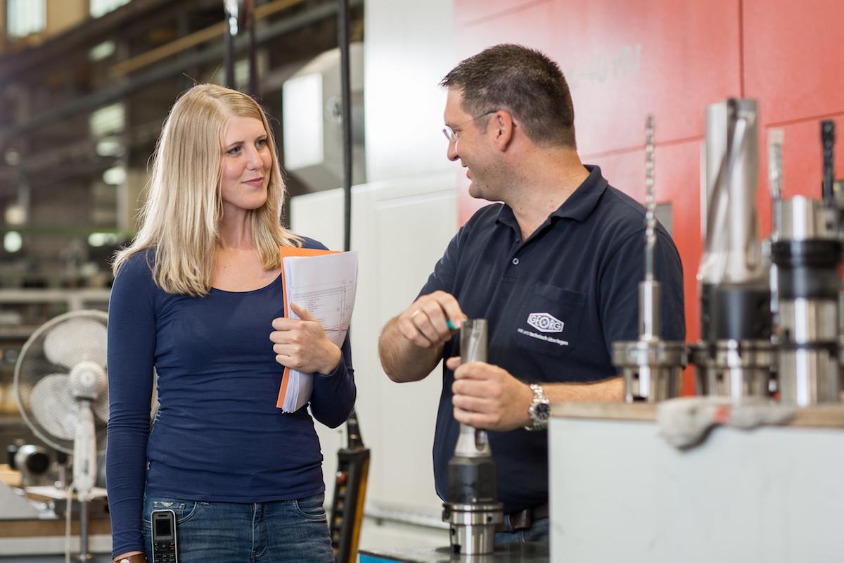 Eine Frau und ein Mann unterhalten sich in einer Fabrik
