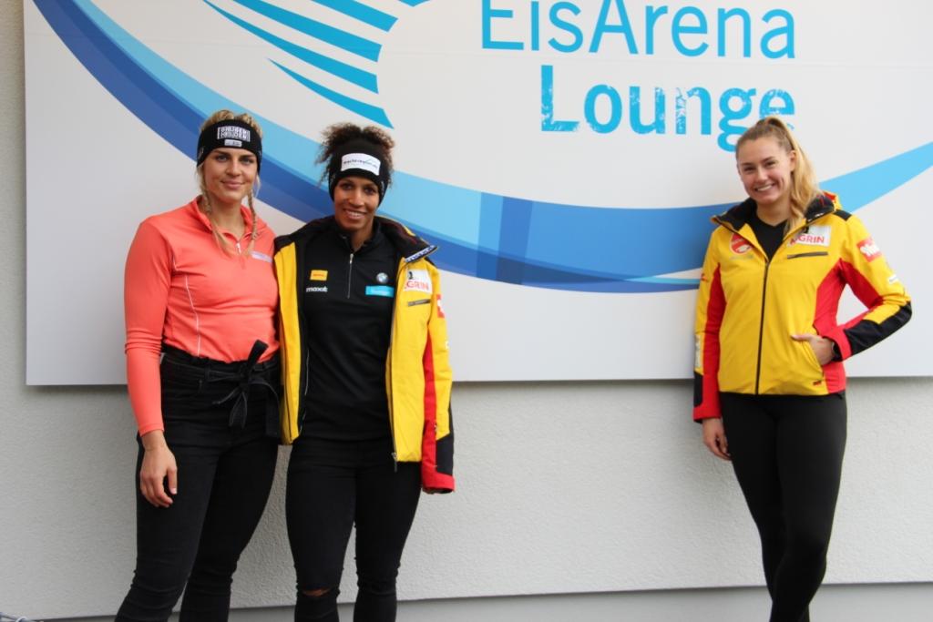 Drei Bobfahrerinnen stehen in Trainingskleidung vor einer Wand