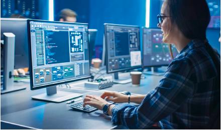 Frau sitzt vor Computer, weitere Bildschirme im Hintergrund