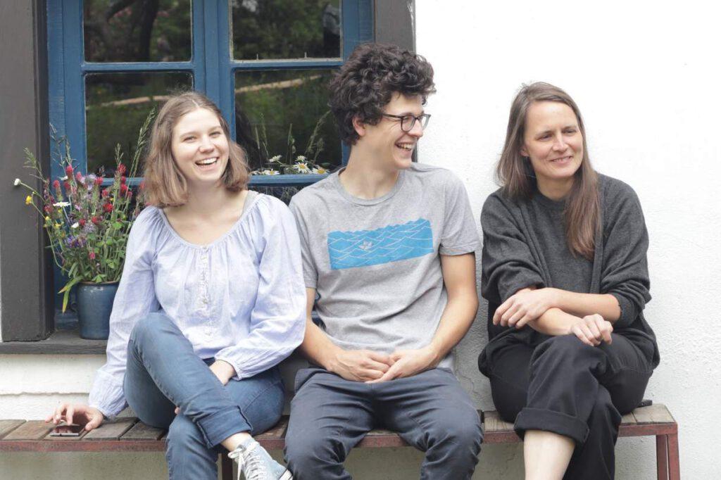 drei Menschen sitzen auf einer Bank
