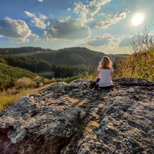 Frau sitzt auf Felsen vor Berglandschaft
