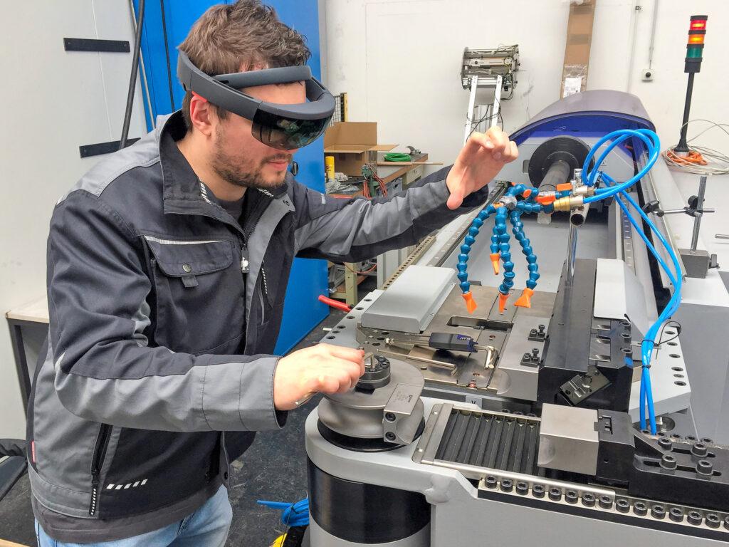 Mann mit AR-Brille steht an einem Arbeitsplatz