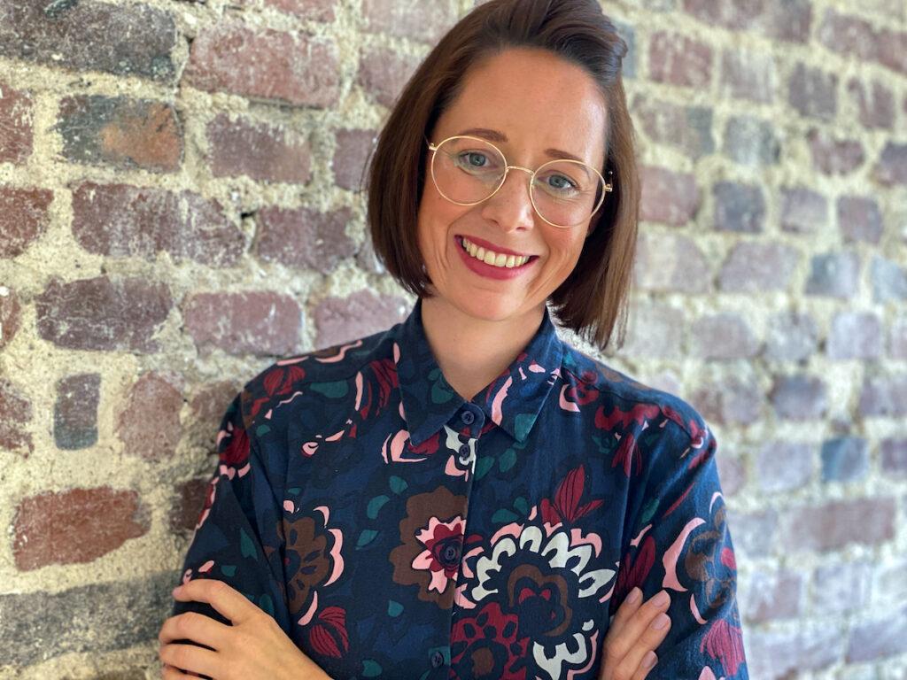 Eine lächelnde junge Frau mit Brille steht vor einer Backsteinwand
