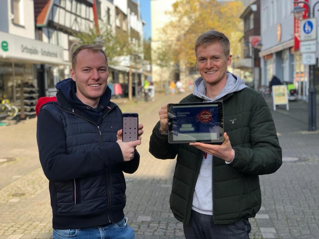 zwei Männer mit einem Smartphone und Tablet in der Hand