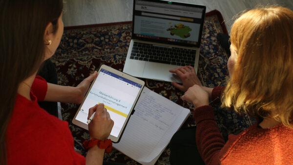 zwei Mädchen sitzen vor einem Laptop und einem Tablet