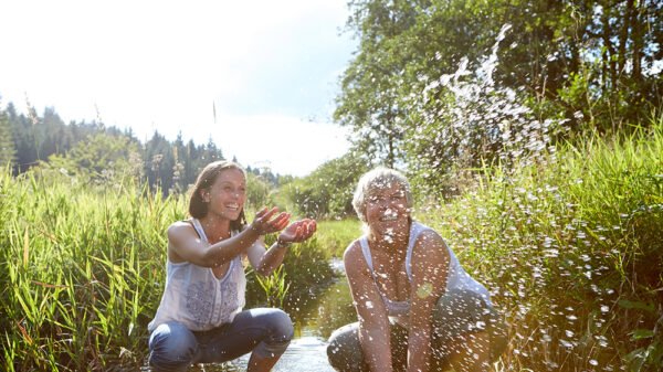 Zwei Frauen knien in einem Bach und spritzen mit Wasser