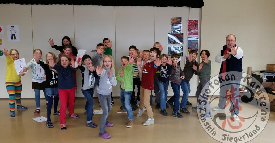 Gruppe von Kindern mit Mann, die die Hände nach vorne zeigen