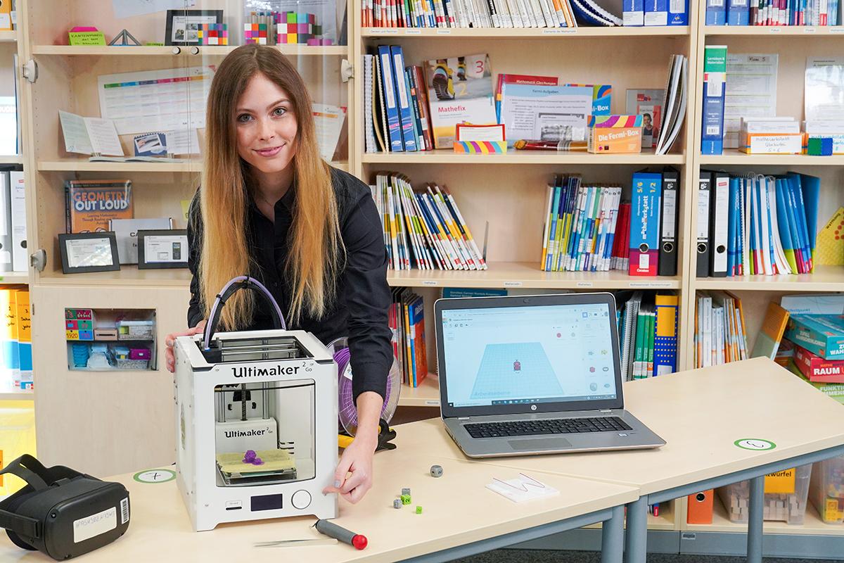 Frau steht hinter einem Tisch mit 3D-Drucker und Laptop