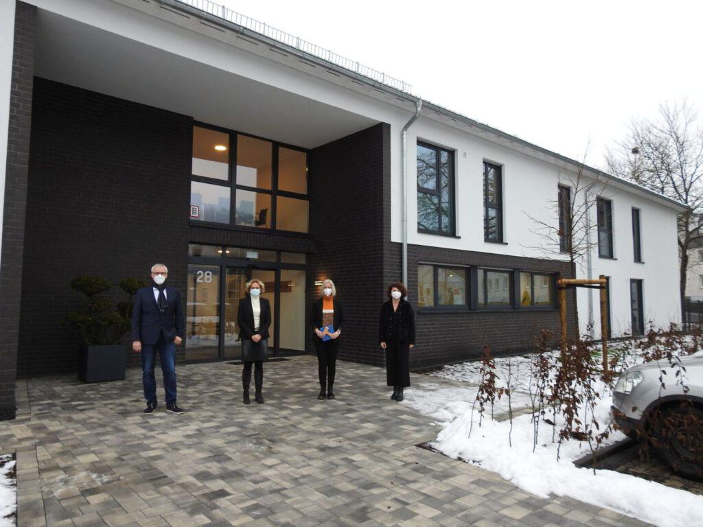 vier Menschen stehen vor einem Gebäude