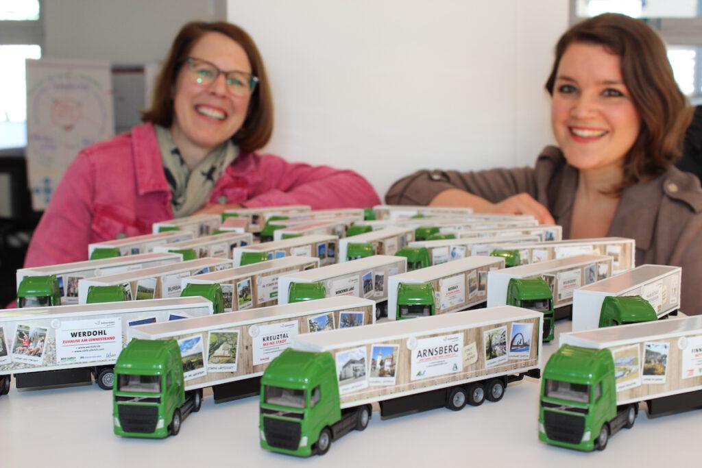 Zwei Frauen neben vielen kleinen Miniatur-Lkw