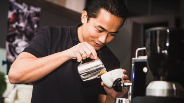 Mann gießt Kaffee in Tasse