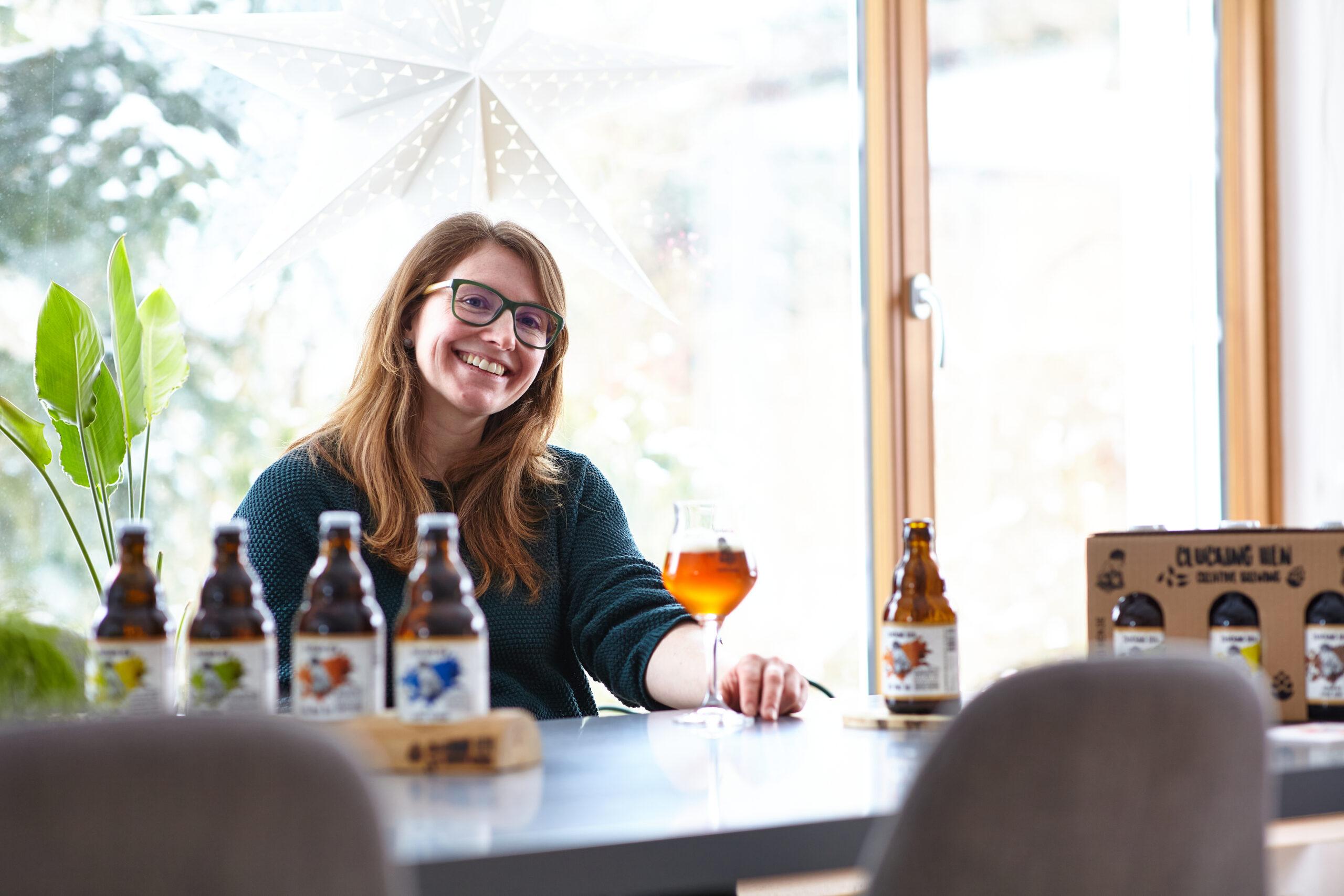 Frau mit Bier sitzt am Tisch