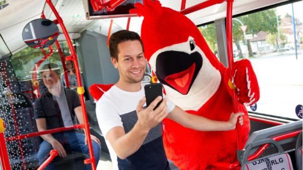 Mann mit Handy steht im Bus neben Vogel-Maskottchen