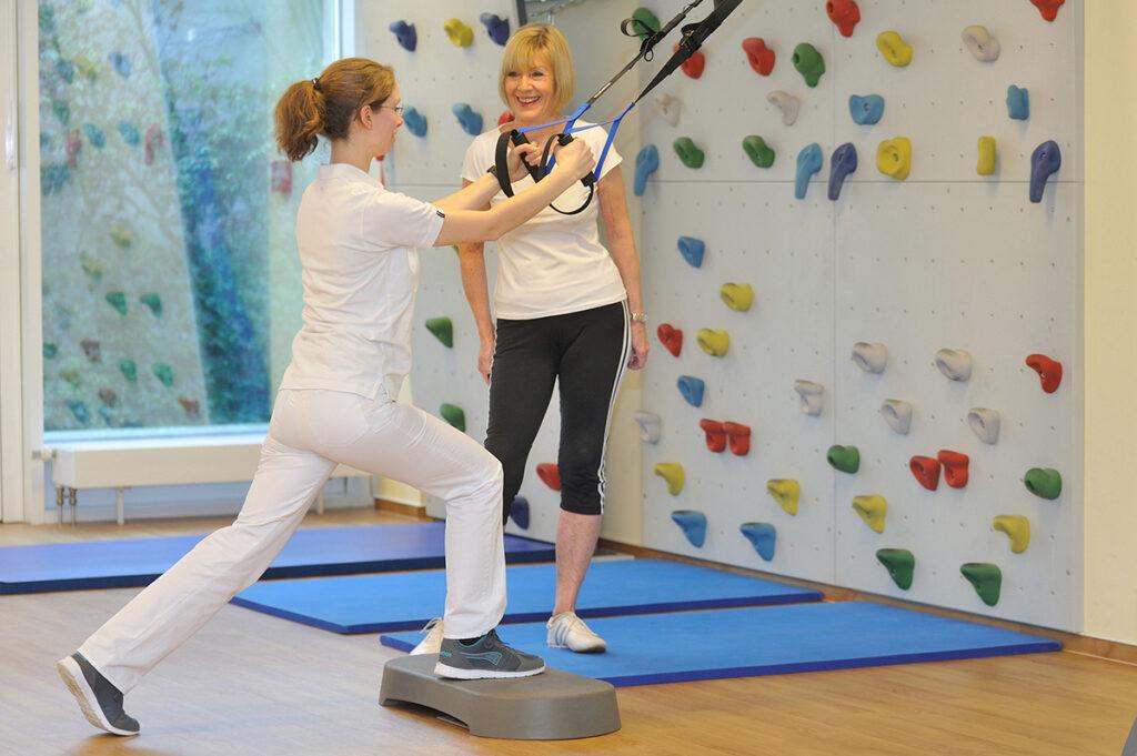 Frau im Vordergrund macht Sportübungen, eine zweite Frau hilft ihr.