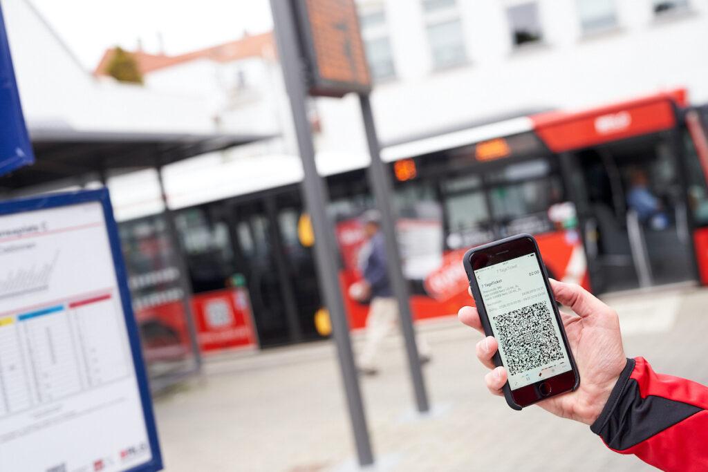 Eine Person hält ein Smartphone in der Hand. Im Hintergrund ist ein Bus.