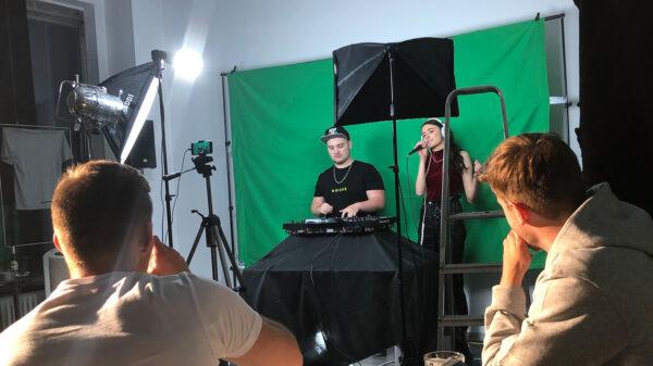 Zwei junge Menschen schauen auf eine Bühne, wo eine Sängerin und ein DJ stehen