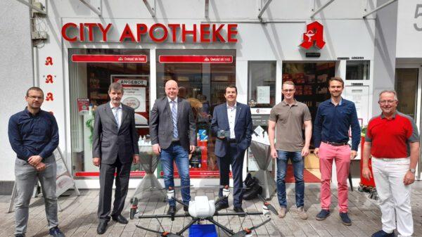 Sieben Personen stehen mit einer Paketdrohne vor einer Apotheke