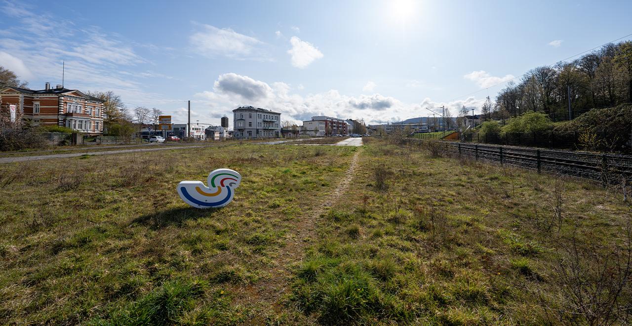 Große Wiesenfläche mit Häusern und blauem Himmel im Hintergrund