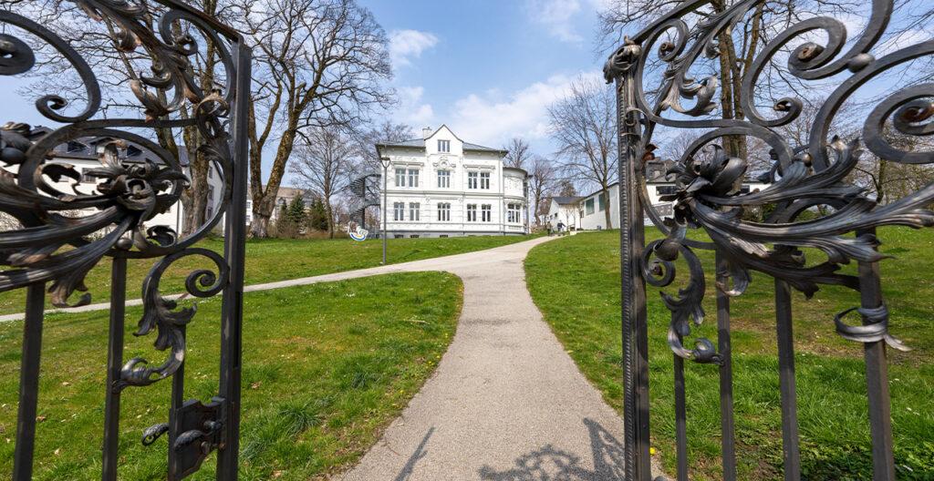 Blick durch ein geöffnetes eisernes Tor, das zu einem grünen Park mit einer Villa führt