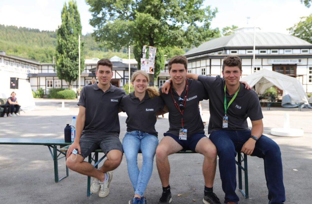 Vier junge Menschen sitzen auf einer Bank und schauen in die Kamera