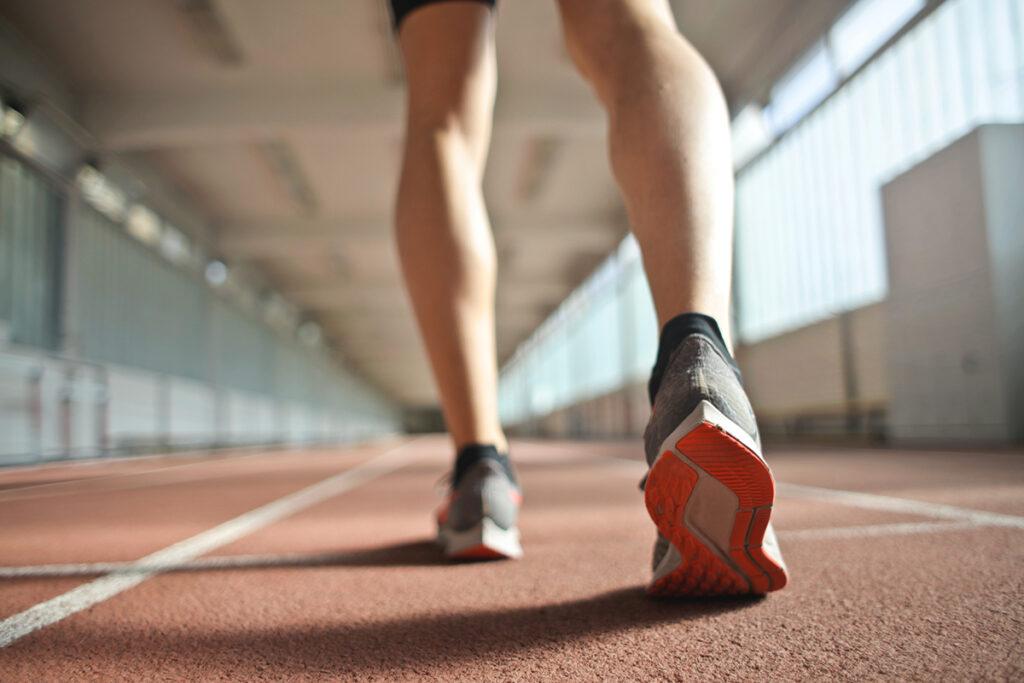 Beine eines Sportlers, der über eine Rennbahn geht