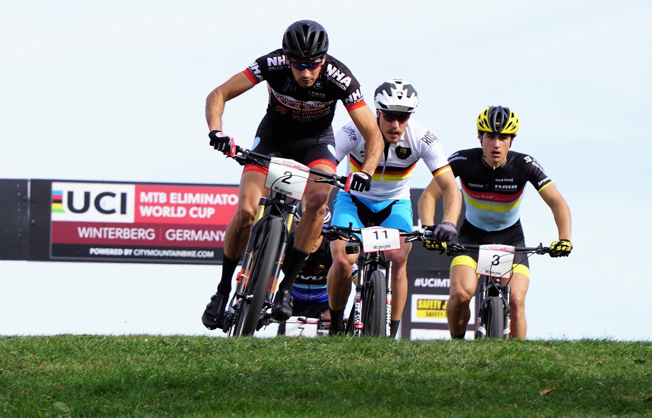 Drei Radfahrer in Sportkleidung fahren eng nebeneinander eine Wiese hinunter