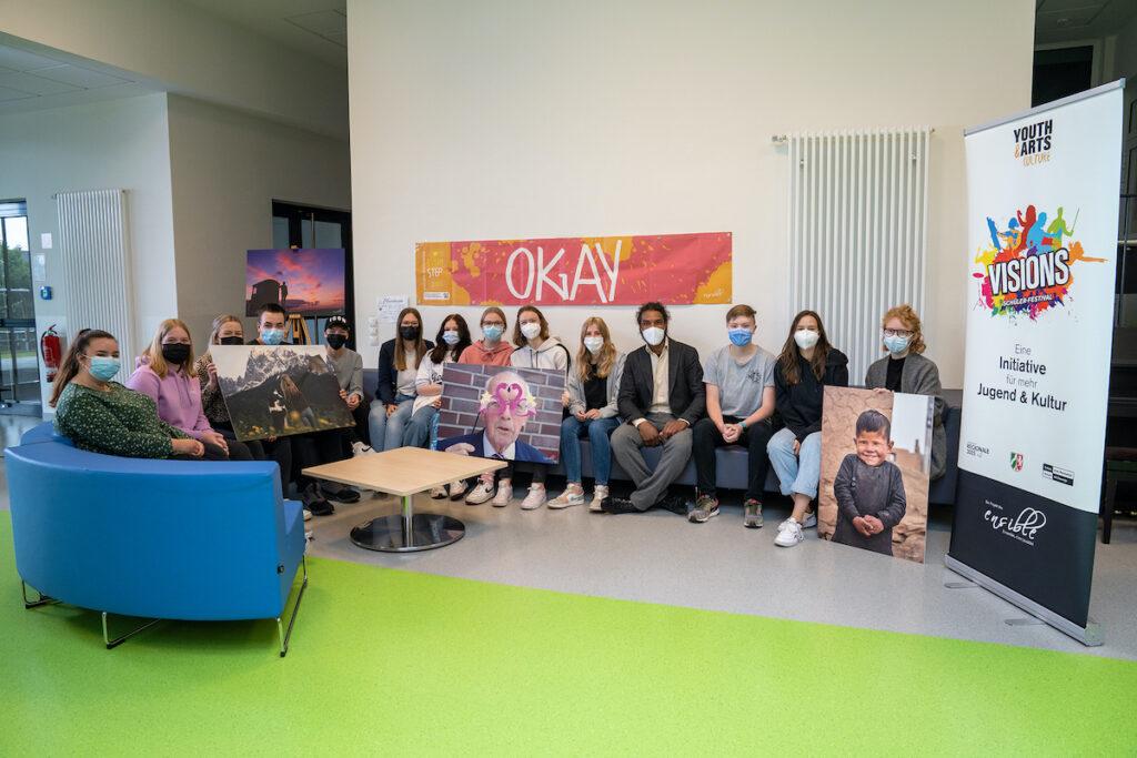 13 Jugendliche sitzen in einem Halbkreis und halten Bilder in der Hand, mit der sie an der Jugendkunstgalerie teilgenommen haben