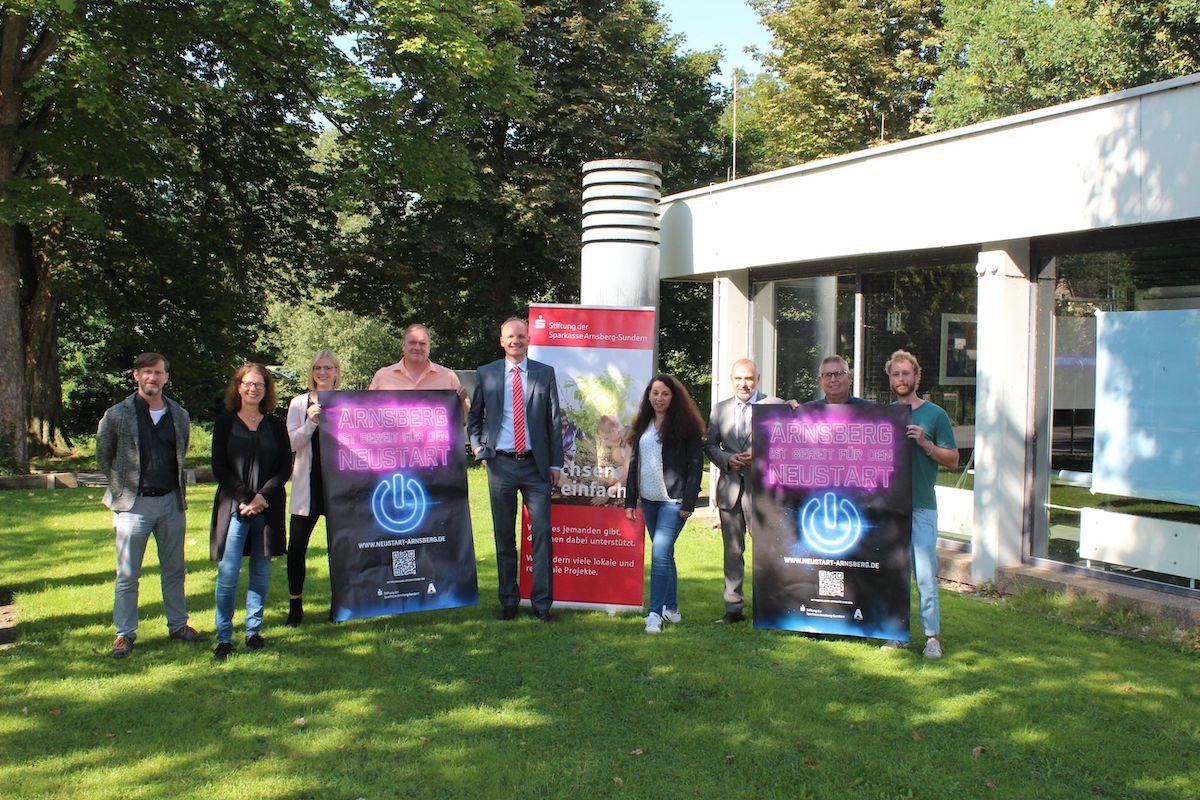 Neun Personen stehen auf einer Wiese und halten Plakate für die neue Kampagne in der Hand